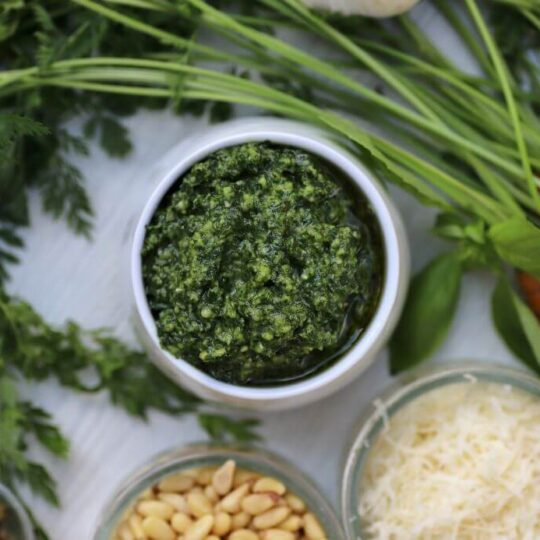 Green pesto in white bowl surrounded by whole carrots and ingredients.