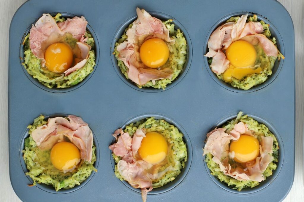 Raw eggs and ham sit in hash brown cups before baking.