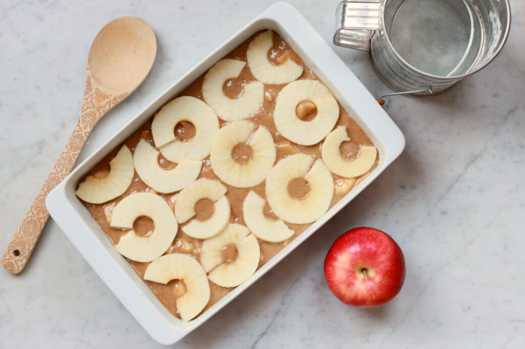 An unbaked cake topped with apple slices.