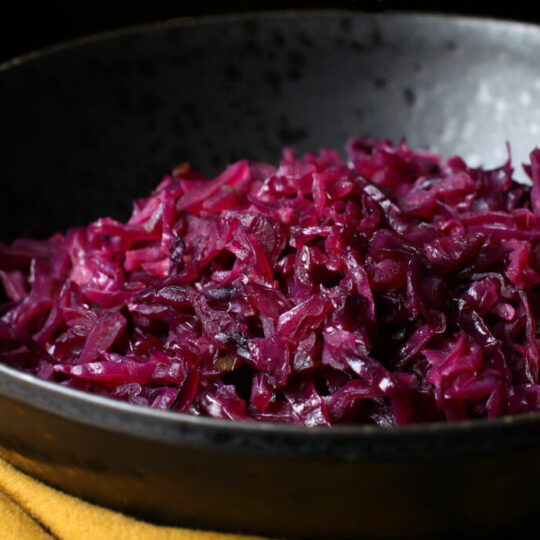 Bright purple shredded red cabbage in a black bowl.