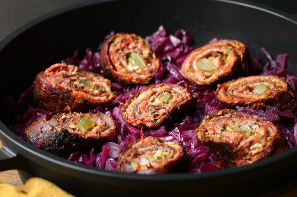 Cooked meat rolls sitting on top of red cabbage in a black pan.