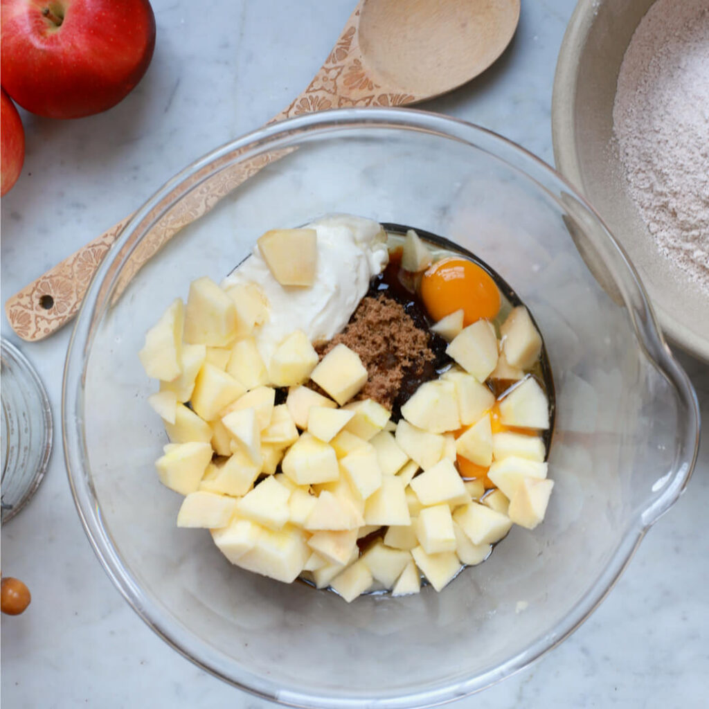 A clear mixing bowl filled with apple chunks and cake ingredients.