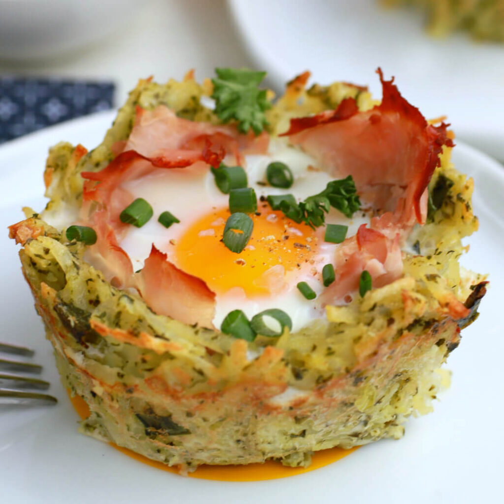 A baked yellow yolked egg with ham sits in a nest of hash browns.