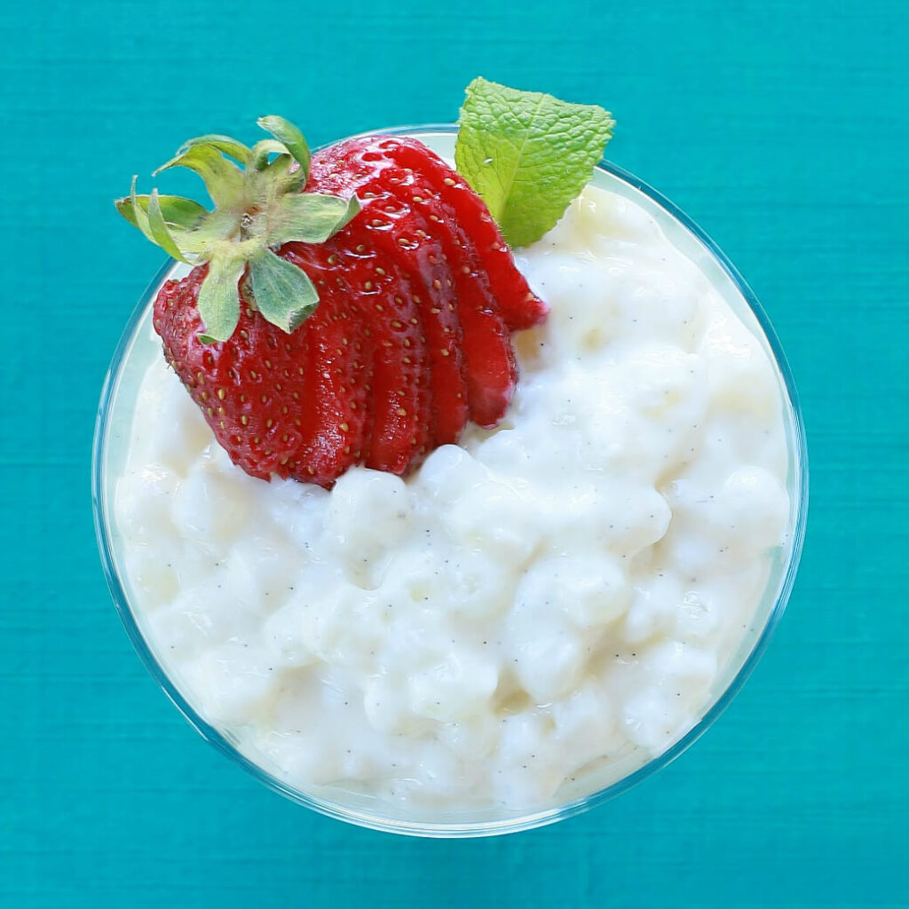 Overhead view of creamy tapioca pudding topped with sliced strawberries on a aqua background.
