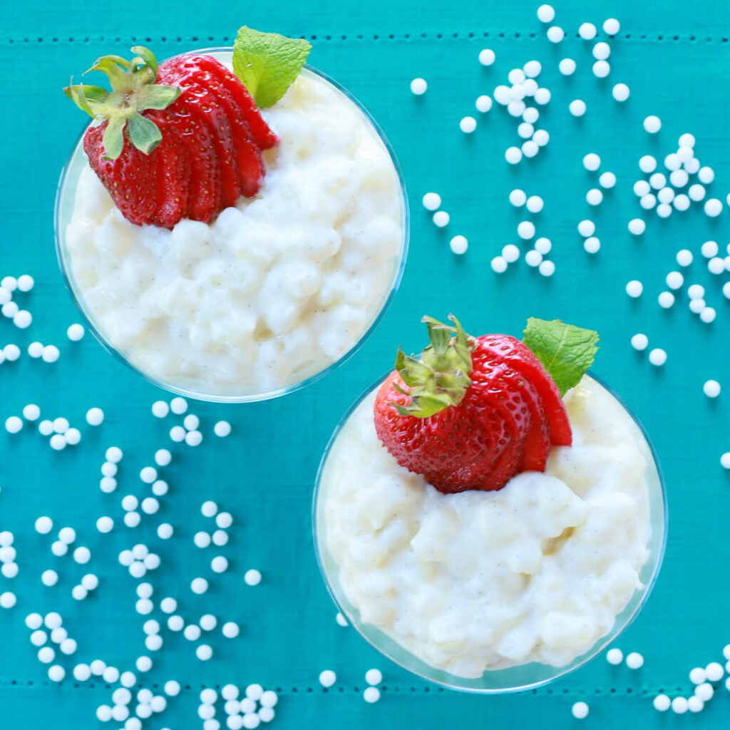 Two glass dessert bowls filled with creamy tapioca pudding topped with sliced strawberries.