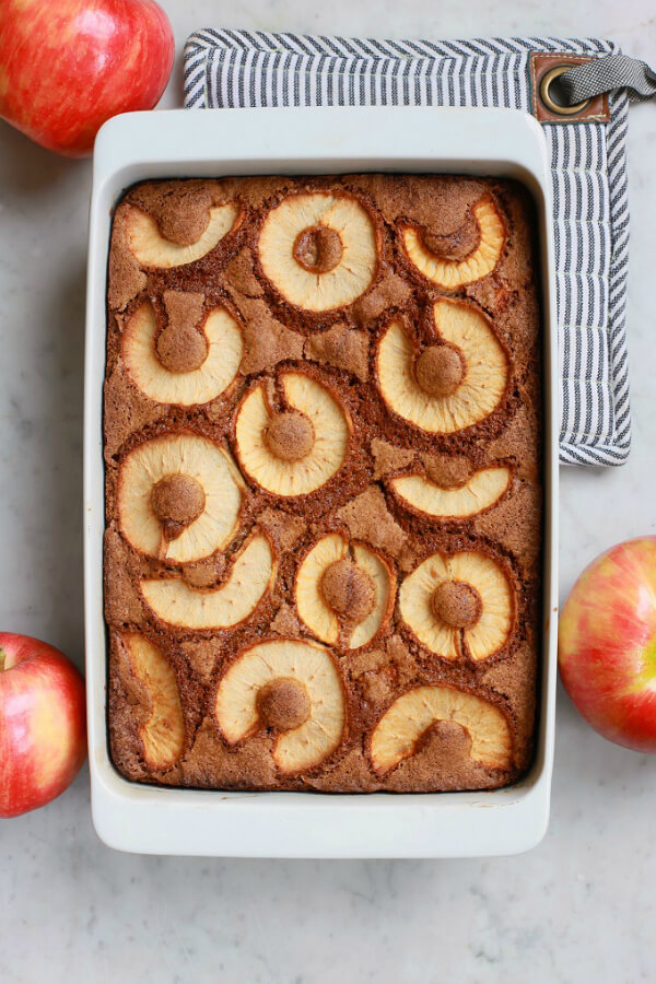 A baked cake topped with apple slices.