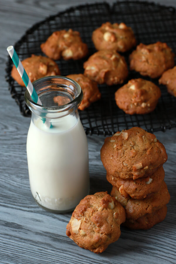Golden baked cookies cooling on a black baking rack next to a bottle of milk.