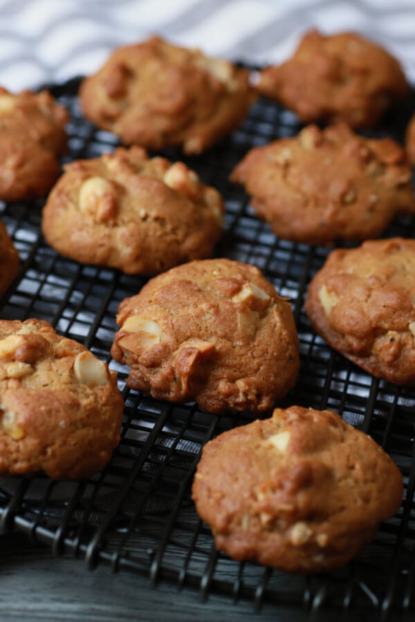 Golden baked cookies cooling on a black baking rack.
