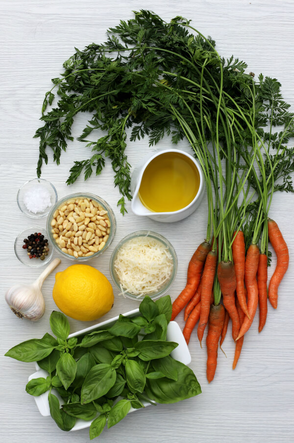 Ingredients needed to make carrot top pesto including carrot greens, pine nuts, olive oil, Parmesan cheese, basil, lemon, and garlic.