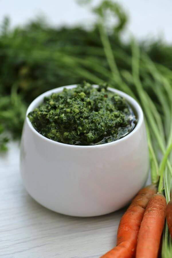 Green pesto in white bowl surrounded by whole carrots.