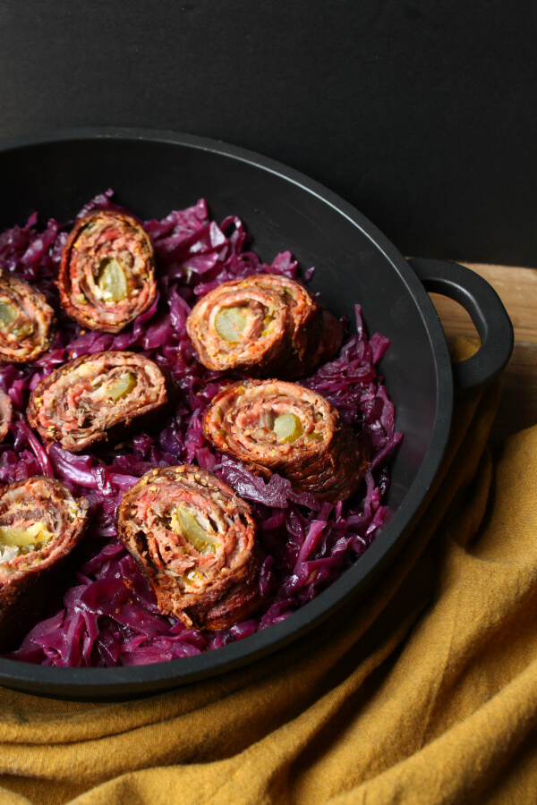 Beef and bacon rolled around a pickle sitting on a bed of red cabbage.