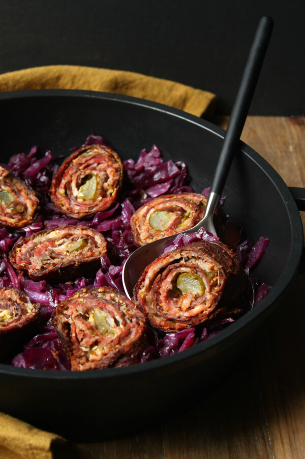 One Beef and bacon roll in a spoon above a pan of more meat rolls sitting on a bed of red cabbage.