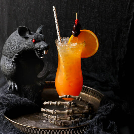 A dark scene featuring a plastic black rat and an icy bright orange cocktail in a tall glass.