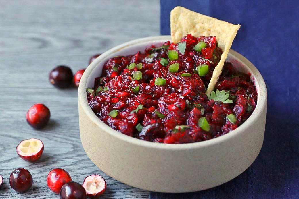 A tortilla chip in a white bowl filled with bright red cranberry salsa topped with fresh chopped cilantro and jalapenos.