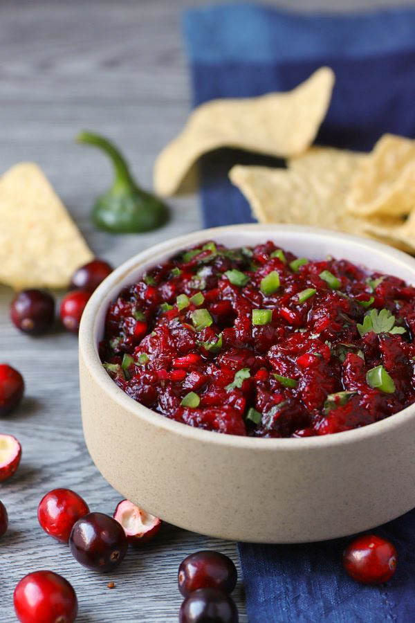 A white bowl filled with bright red cranberry salsa topped with fresh chopped cilantro.