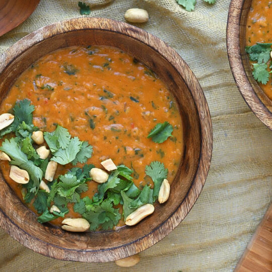 A creamy orange soup in a wooden bowl flecked with greens and garnished with cilantro and peanuts.