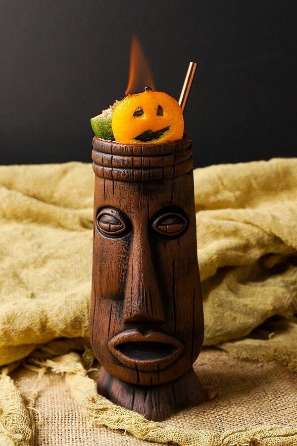 A tall brown Tiki mug topped with a flaming jack o lantern garnish.