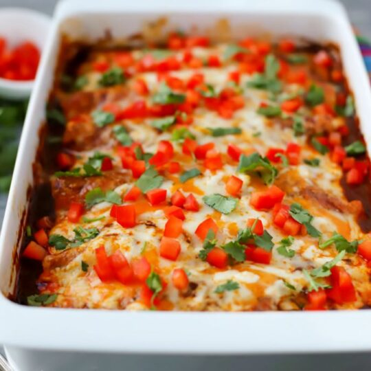 A white baking dish full of cheesy baked enchiladas topped with cilantro and red peppers.
