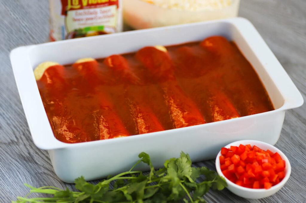 Red enchilada sauce topped enchiladas in a white baking pan.