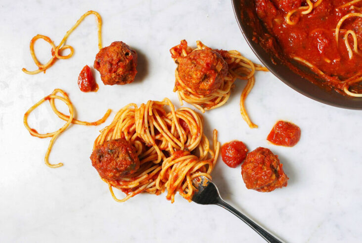 A group of saucy meatballs and coiled spaghetti on a white marble background.
