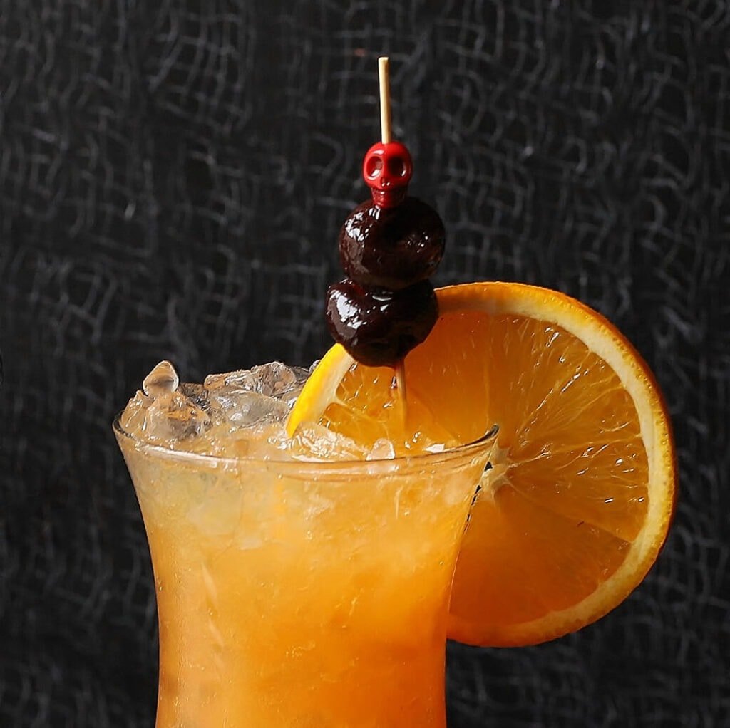 Close up of an orange cocktail garnishes with two cherries and an orange wheel.