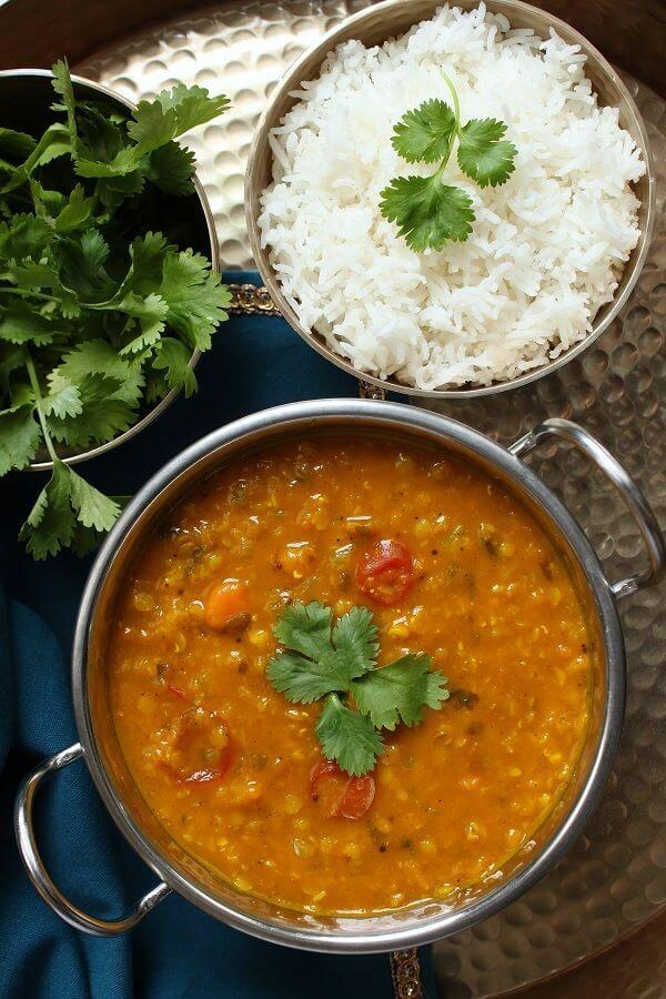 A silver serving bowl filled with red lentil daal and vegetables.