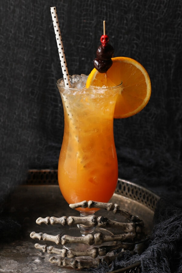 A dark scene featuring an icy bright orange cocktail in a tall glass held by a skeleton hand.