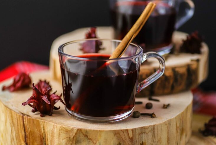 A clear glass cup filled with red sorrel drink and a cinnamon stick.