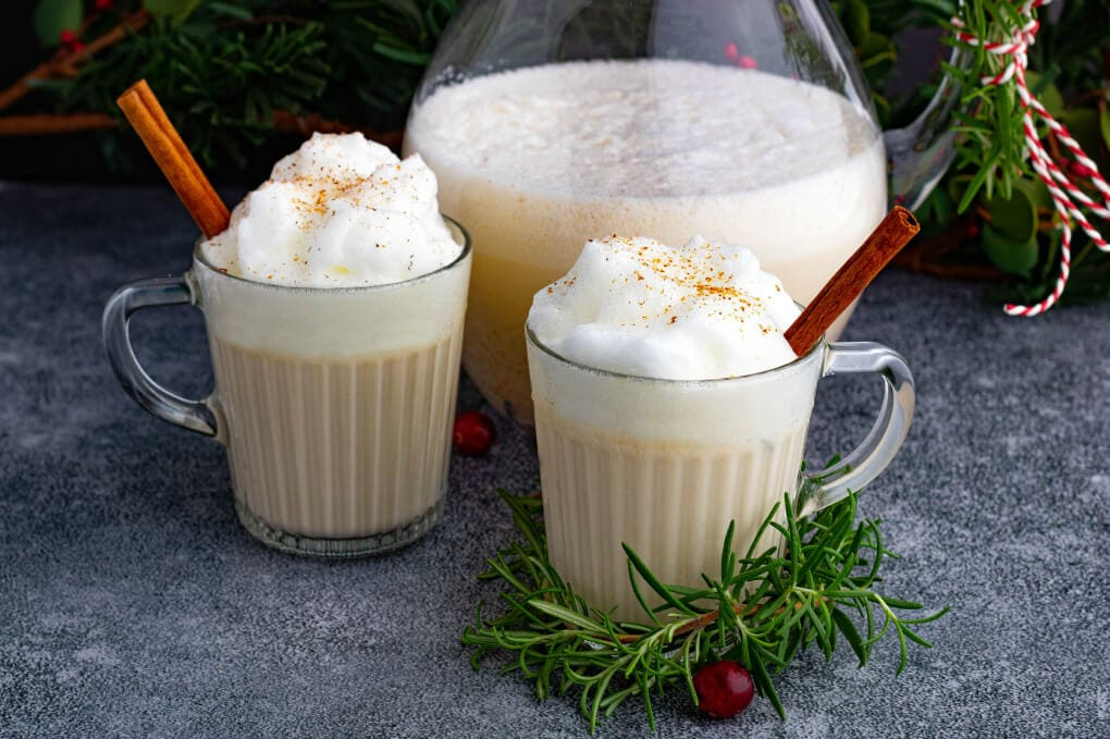 Two glass mugs filled with creamy eggnog topped with foam and grated nutmeg.
