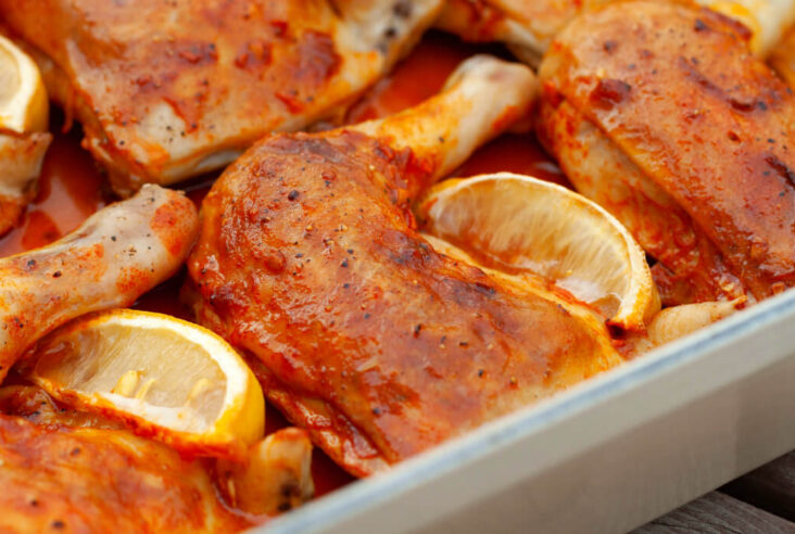 Orange coloured Baked Chicken Legs with lemon wedges.