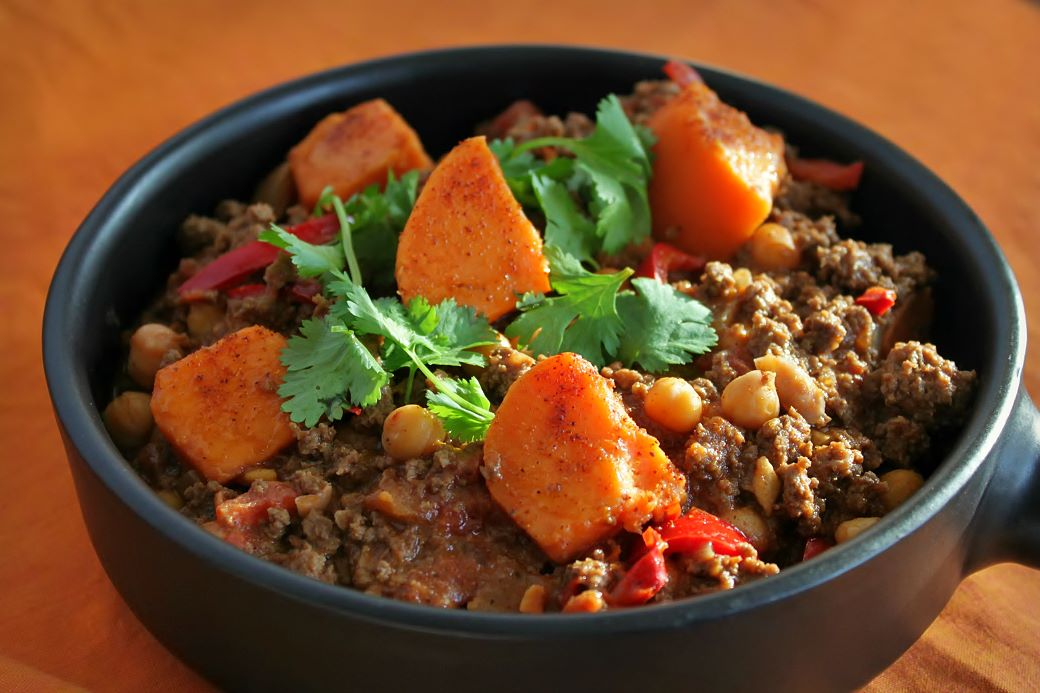 A black bowl filled with ground bison chili, peppers, chick peas, and large orange sweet potato bites.