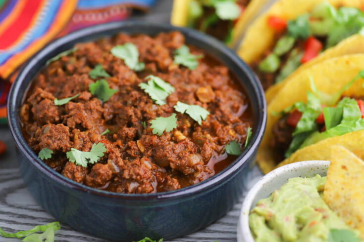 A bowl full of cooked spiced ground beef beside tacos and guacamole.