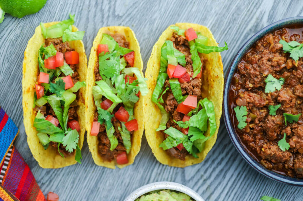 Three filled hard shell tacos surrounded by lime wedges, guacamole and a bowl of crockpot taco meat.