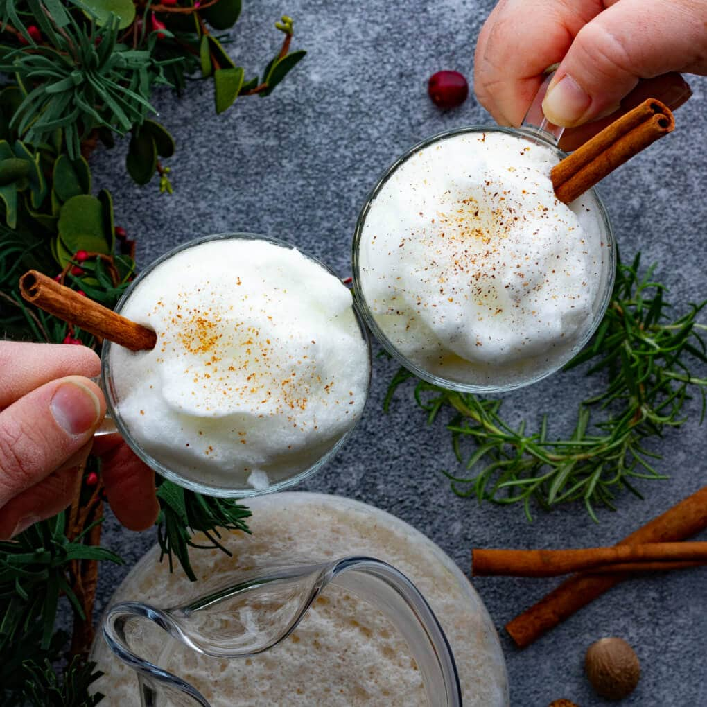 Two hands click glasses filled with bourbon eggnog together in holiday cheers.