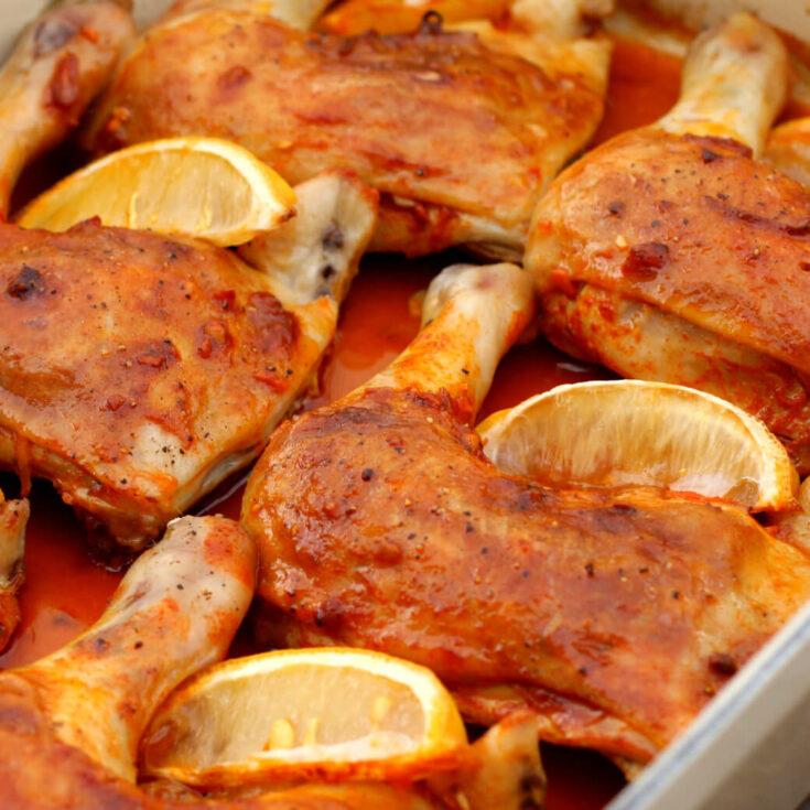 Orange coloured Baked Chicken Legs with lemon wedges.