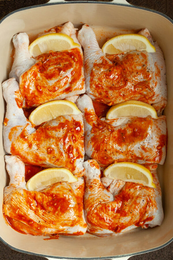 Raw chicken legs coated with orange paprika paste.