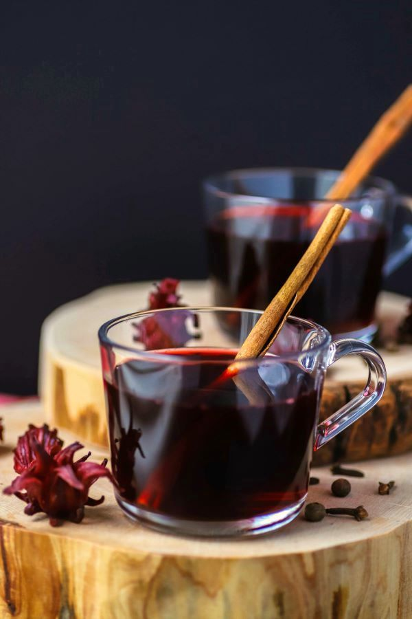Two clear glass cups filled with red sorrel drink and a cinnamon stick.