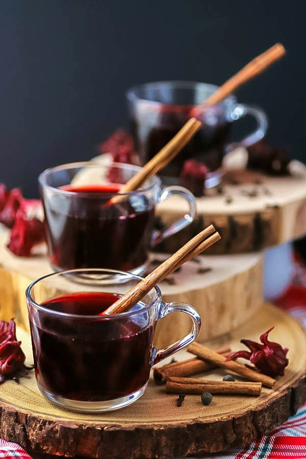 Three clear glass cups filled with red sorrel drink and a cinnamon stick.