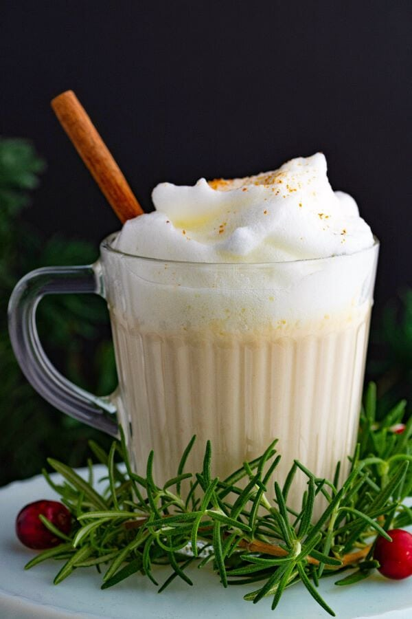 One glass mug filled with creamy bourbon eggnog with cinnamon stick on a white pedestal.