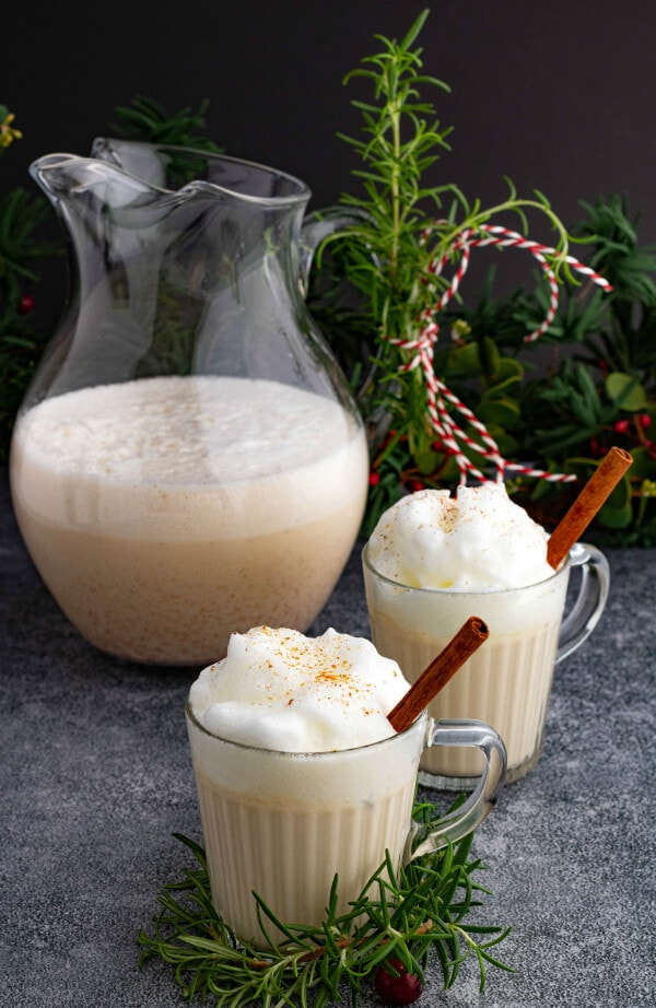 Two glass mugs and a pitcher filled with creamy eggnog topped with foam and grated nutmeg.