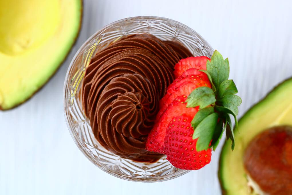 A crystal glass filled with dark chocolate avocado mousse topped with a strawberry.