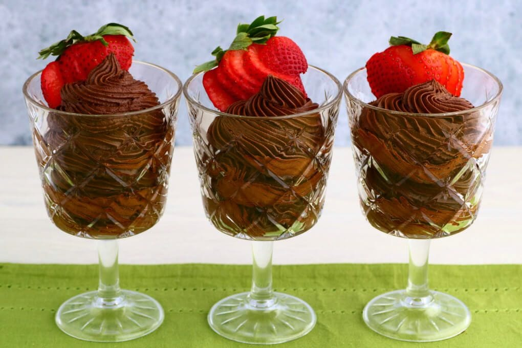 Crystal glasses filled with dark chocolate avocado mousse topped with a strawberry.
