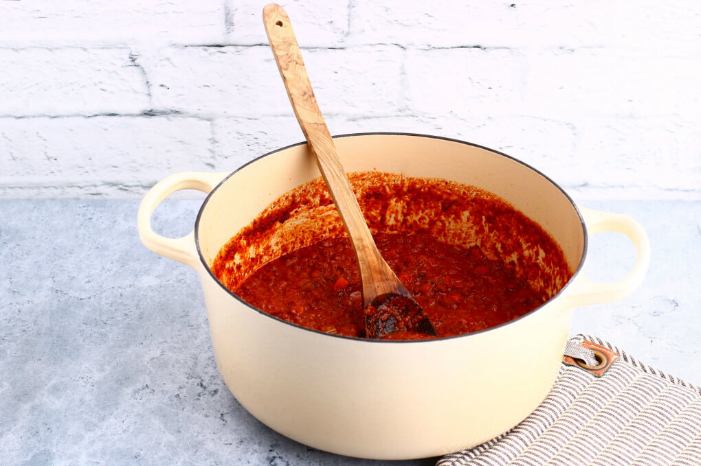 A pot filled with bright red rich meat sauce.