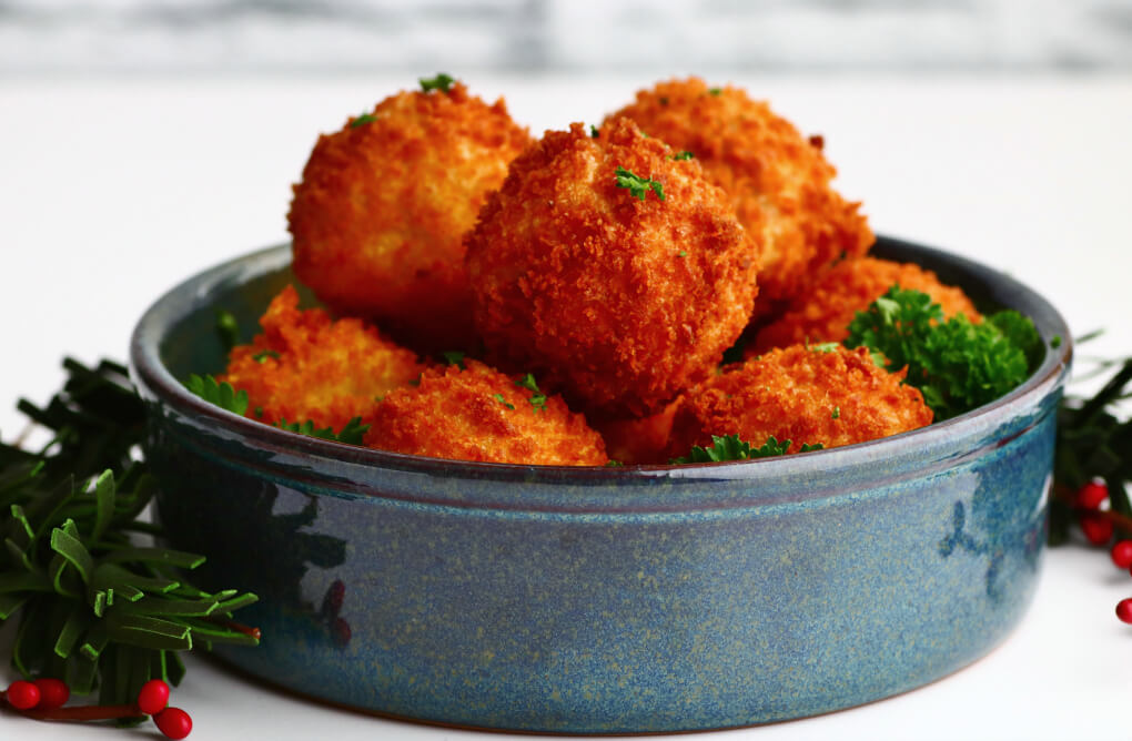 A blue bowl filled with golden fried goat cheese balls.