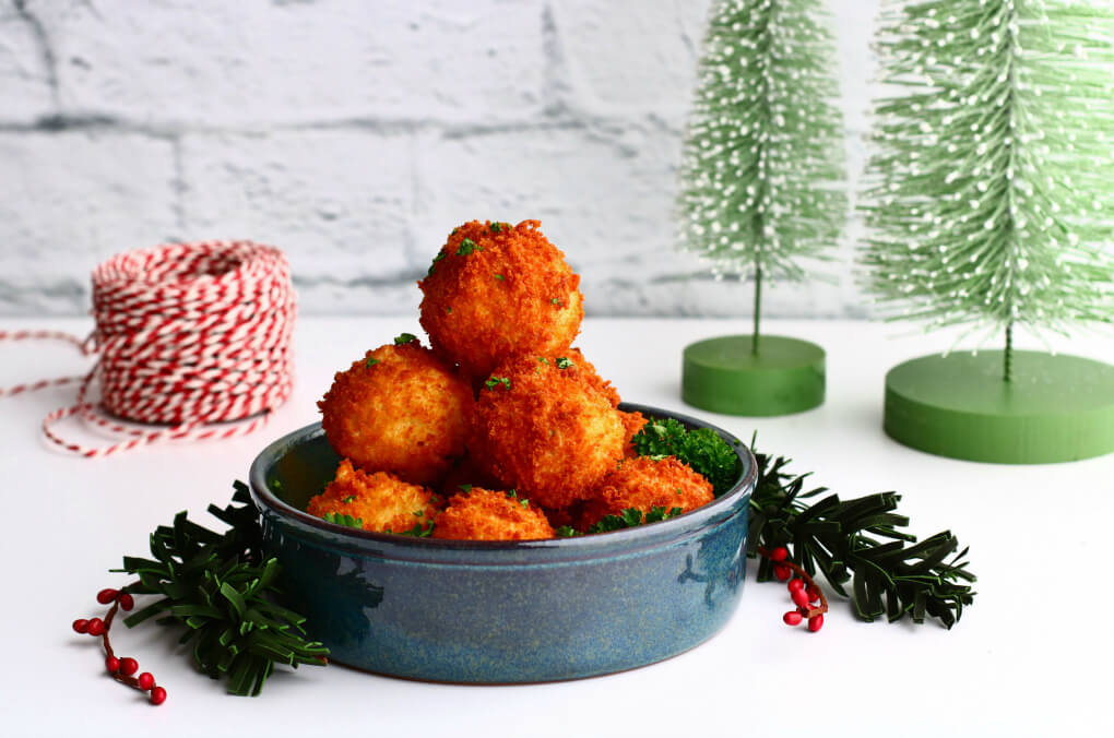 A blue bowl filled with golden fried goat cheese balls surrounded by Christmas decorations.