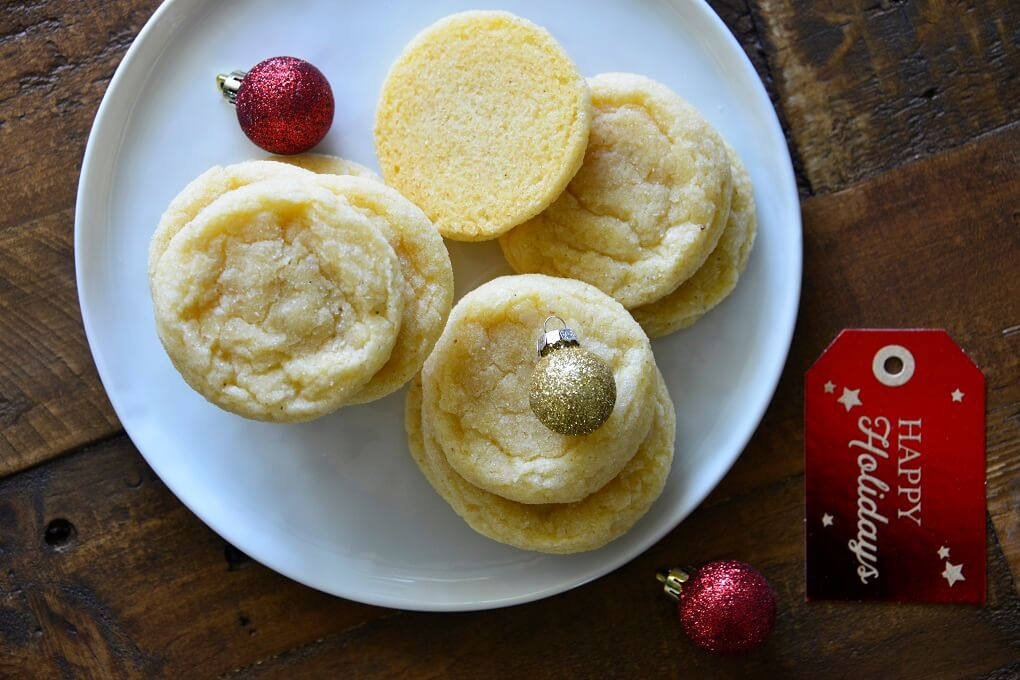Eggnog Cookies on a white plate with Christmas ball decorations.