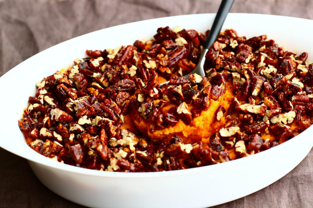 A white oval serving dish containing Sweet Potato Crunch  mashed sweet potatoes topped with chopped pecans.