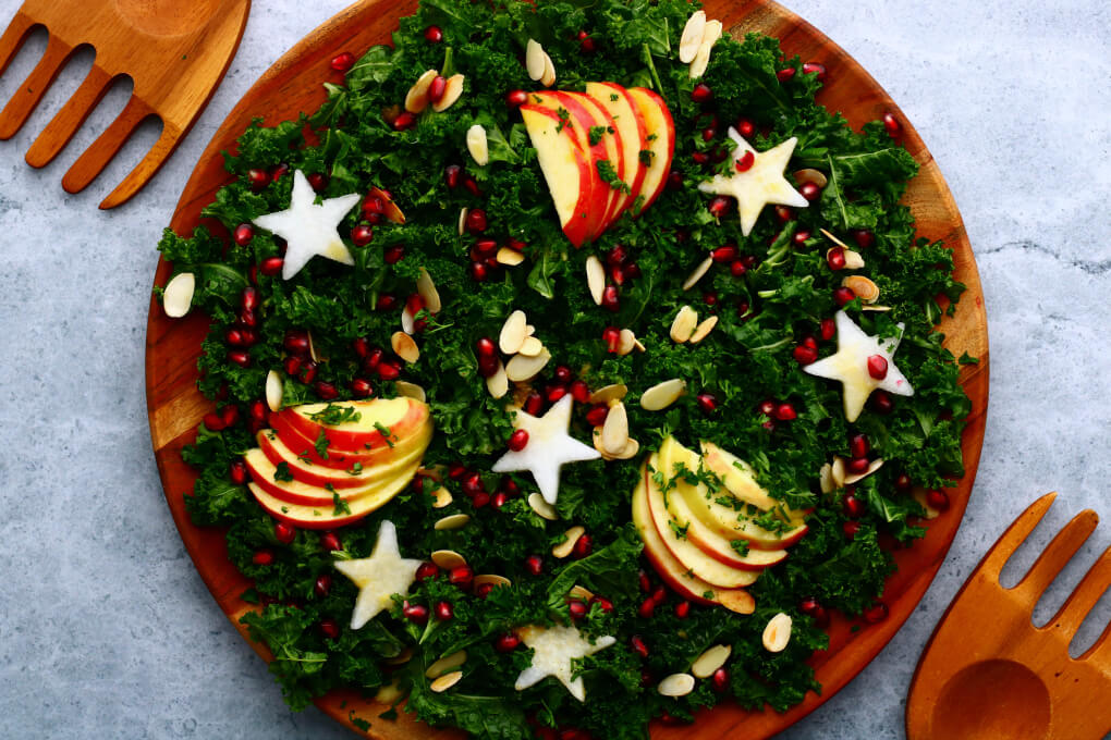 A leafy green massaged kale salad topped with apple slices, daikon stars, almonds, and pomegranate seeds.