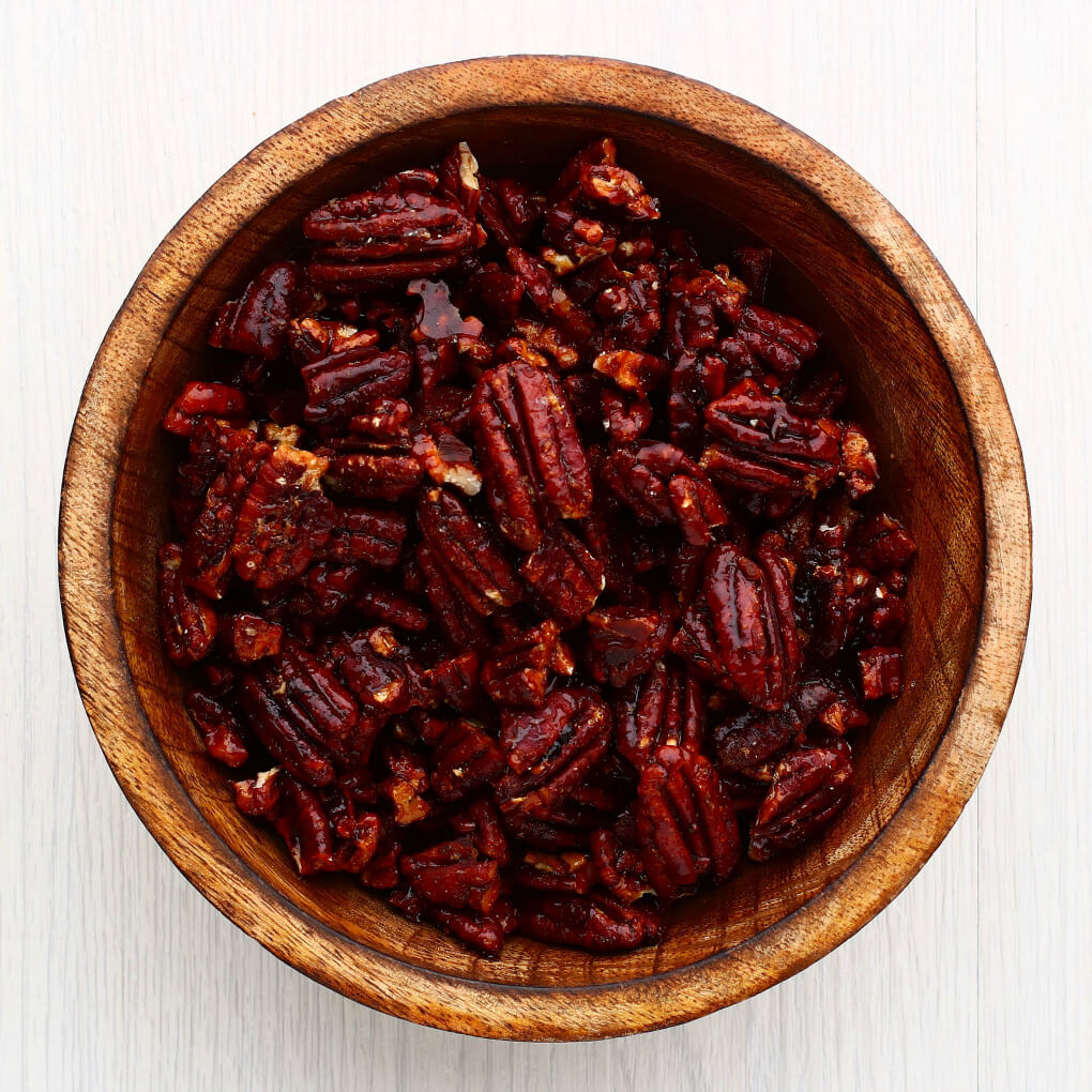 A wooden bowl containing candied nuts.