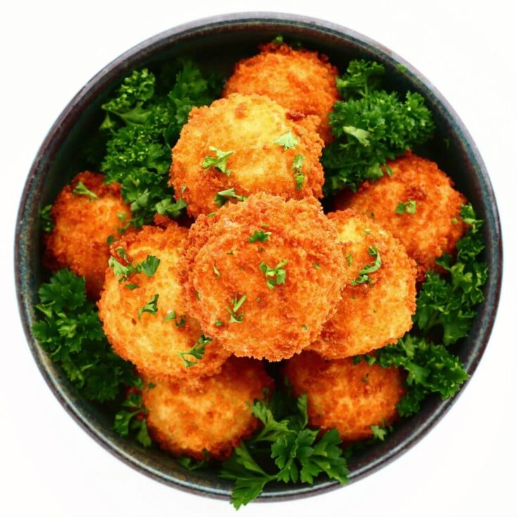 Overhead view of a blue bowl filled with golden fried goat cheese balls.